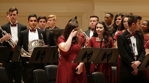 A performer in the the Marjory Stoneman Douglas High School Wind Symphony wipes away tears after a performance at Carnegie Hall in New York, Tuesday, March 6, 2018. Three weeks after a gunman killed 17 people at their high school, the students from Parkland, Fla., followed through with a long-planned Carnegie Hall performance. (AP Photo/Seth Wenig)