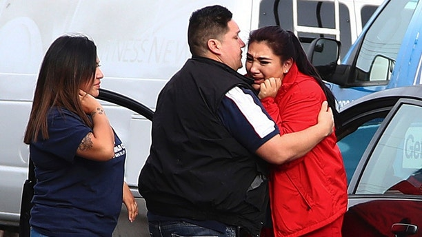 Fernando Juarez, 36, of Napa, center, embraces his 22-year-old sister Vanessa Flores, right, at the Veterans Home of California on Friday March 9, 2018. in Yountville, Calif. Flores, who is a caregiver at the facility, exchanged texts with family while sheltering in place. A gunman took at least three people hostage at the largest veterans home in the United States on Friday, leading to a lockdown of the sprawling grounds in California, authorities said. (AP Photo/Ben Margot)
