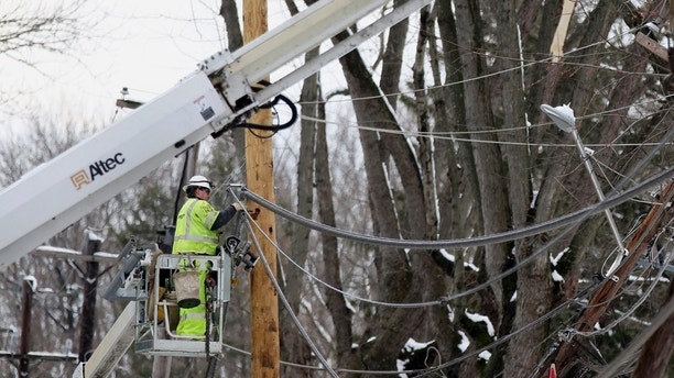 Crews work to replace utility poles in Fairless Hills, Pa. on Thursday, March 8, 2018. Pennsylvania utility companies say more than 110,000 customers were  without power Thursday morning following the state's second major snowstorm in less than a week. (Tim Tai/The Philadelphia Inquirer via AP)