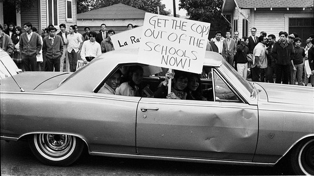 """This March 1968 photo provided by the UCLA Chicano Studies Research Center, protesters in a car drive by with a sign that reads """"Get the Cops Out of the Schools Now!"""" during a walkout by students at Theodore Roosevelt High School in Los Angeles. Participants of a 1968 Los Angeles high school walkout over dropout rates, paddle beatings for speaking Spanish and other issues say they are hearing echoes of those protests in the voices of outraged students at Marjory Stoneman Douglas High School in Parkland, Florida, where 17 people died in a mass shooting. Theodore Roosevelt was one of the several high schools joining the protest. (Devra Weber/La Raza Photograph collection/UCLA Chicano Studies Research Center via AP)"""