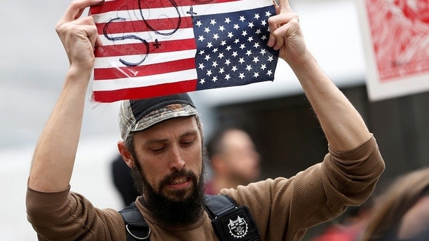 A demonstrator holds an inverted U.S. flag during a rally to denounce raids to apprehend immigrants without legal status, according to organizers, outside the United States Immigration & Customs Enforcement (ICE) office in San Francisco, California, U.S., February 28, 2018. REUTERS/Stephen Lam - RC17FA018C80