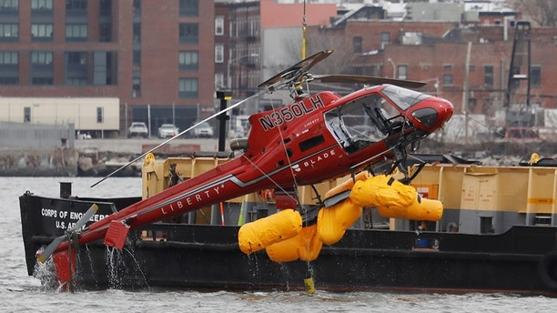 Photo of: Copper down at 88th Street and the FDR in Manhattan. Believed to be helicopter c   rash pilot Richard Vance.  This chopper went down in the East River  Photo credit: G.N.Miller/NYPost (Staff Photographer).  Note: The First Responders removing the first person from the water (possibly) the pilot.