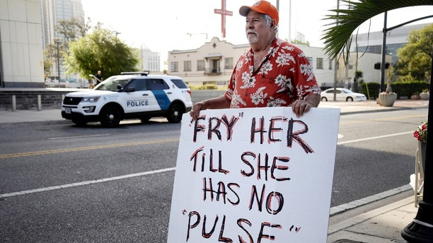 Bob Kunst protests against the widow of the Pulse nightclub shooter Noor Salman, who faces charges of aiding her husband in killing 49 people in 2016, outside the federal court house in Orlando, Florida, U.S. March 1, 2018.  REUTERS/Joey Roulette - RC1B1493D500