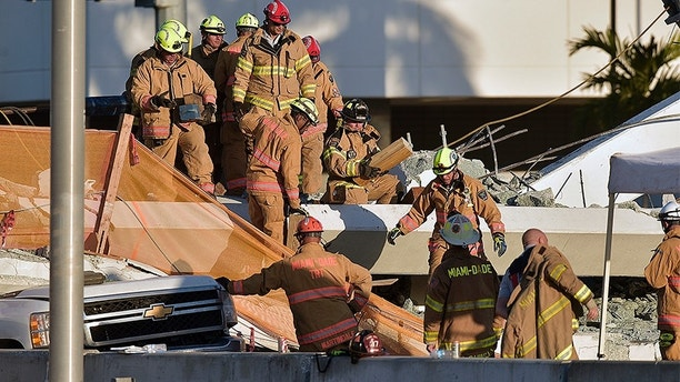 Miami-Dade Fire Rescue firefighters work on a brand new, 950-ton pedestrian bridge that collapsed in front of Florida International University, Thursday, March 15, 2018, in Miami. Florida officials said Thursday that several people have been found dead in the rubble of a collapsed South Florida pedestrian bridge where the frantic search for any survivors continued past nightfall. (Michael Laughlin/South Florida Sun-Sentinel via AP)