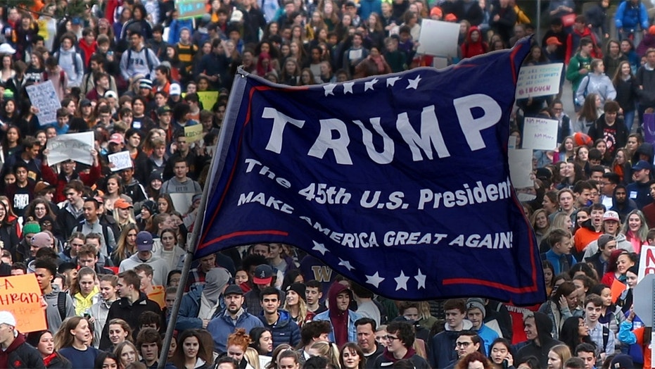 """A student carrying a """"Trump"""" flag was assaulted in Minnesota during the National School Walkout Day."""