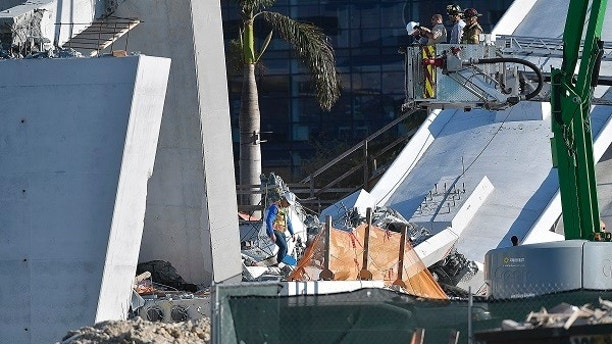 Miam-Dade Fire Rescue personnel work after a brand new, 950-ton pedestrian bridge collapsed in front of Florida International University, Thursday, March 15, 2018, in Miami. Florida officials said Thursday that several people have been found dead in the rubble of the collapsed South Florida pedestrian bridge where the frantic search for any survivors continued past nightfall. (Michael Laughlin/South Florida Sun-Sentinel via AP)