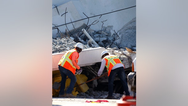 Workers push back a yellow tarp under a section of a collapsed pedestrian bridge, Friday, March 16, 2018 near Florida International University in the Miami area.   The new pedestrian bridge that was under construction collapsed onto a busy Miami highway Thursday afternoon, crushing vehicles beneath massive slabs of concrete and steel, killing and injuring several people, authorities said.   (AP Photo/Wilfredo Lee)