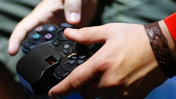 A visitor plays with a 'Playstation' at an exhibition stand at the Gamescom 2009 fair in Cologne August 22, 2009. The Gamescom convention, Europe's leading fair for computer games, runs from August 19 to August 23. REUTERS/Ina FAssbender (GERMANY ENTERTAINMENT SOCIETY) - GM1E58M1NMD01