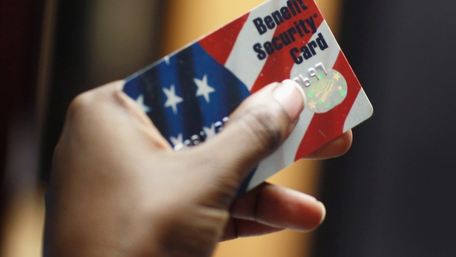 A social worker displays a federal food stamps card in Fort Lauderdale, Fla., Feb. 10, 2011.