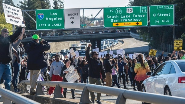 """Hundreds of protesters demonstrating against the fatal police shooting of Stephon Clark shut down Interstate 5 in both directions in downtown Sacramento, Calif., Thursday, March 22, 2018. Protesters decrying this week's fatal shooting of an unarmed black man marched from Sacramento City Hall and onto the nearby freeway Thursday, disrupting rush hour traffic and holding signs with messages like """"Sac PD: Stop killing us!"""" (Renee C. Byer/The Sacramento Bee via AP)"""