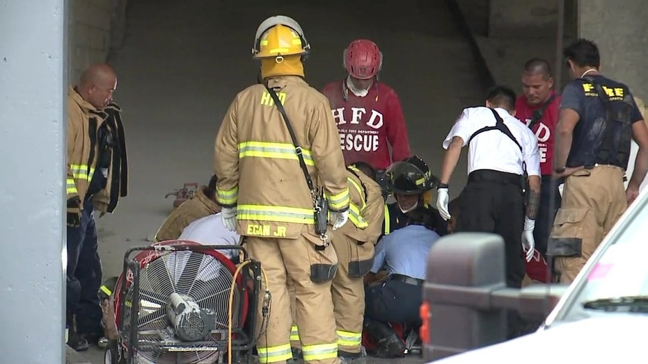 Emergency crews treat a man who was freed from between two buildings in Honolulu, March 23, 2018.