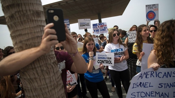 """Israelis and Americans participate in a pro gun control rally in the U.S., the """"March for Our Lives"""", a demonstration which will take place on Saturday in Washington DC and is one of over 800 events planned around the world, outside the U.S. Embassy in Tel Aviv, Israel, Friday, March 23, 2018. (AP Photo/Oded Balilty)"""