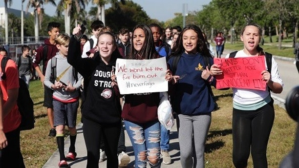 FILE- This March 14, 2018 file photo shows students from Westglades Middle School walking out of their school as part of a nationwide protest against gun violence in Parkland, Fla. Students across the country participate in walkouts Wednesday to protest gun violence, one month after the deadly shooting inside Marjory Stoneman Douglas High School in Parkland, Fla. In the wake of a Valentine's Day shooting that killed 17, a handful of Parkland teenagers are on the cusp of pulling off what could be one of the largest marches in history with nearly 1 million expected in DC and more than 800 sister marches planned across every continent. (AP Photo/Lynne Sladky, File)