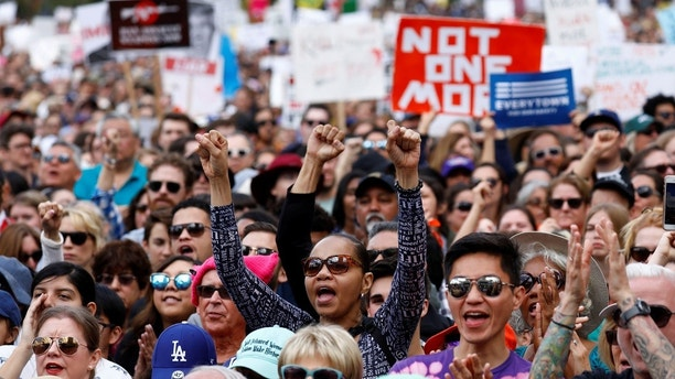 """People hold signs and cheer during """"March for Our Lives"""", an organized demonstration to end gun violence, in downtown Los Angeles, California, U.S., March 24, 2018.  REUTERS/Patrick T. Fallon - RC1332140990"""