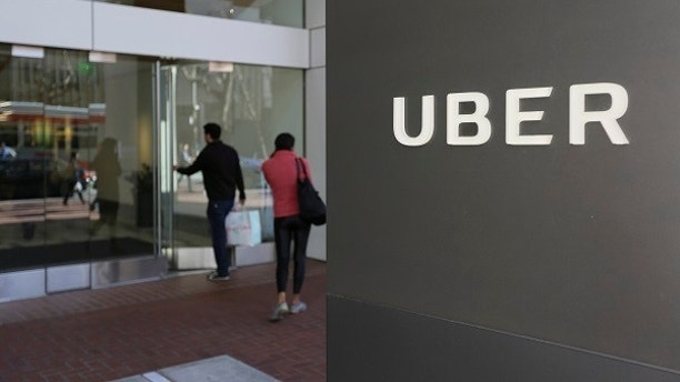 FILE - In this March 1, 2017 file photo, people enter the headquarters of Uber in San Francisco. Uber suspended all of its self-driving testing Monday, March 19, 2018, after what is believed to be the first fatal pedestrian crash involving the vehicles. The testing has been going on for months in the Phoenix area, Pittsburgh, San Francisco and Toronto as automakers and technology companies compete to be the first with the technology. Uber's testing was halted after police in a Phoenix suburb said one of its self-driving vehicles struck and killed a pedestrian overnight Sunday. (AP Photo/Eric Risberg, File)