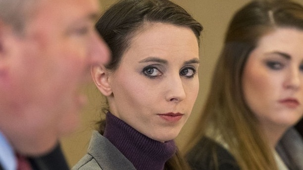 Rachael Denhollander, center, listens to her attorney John Manly speak during a press conference after Michigan sports doctor Larry Nassar was sentenced to 60 years in prison on child pornography charges in Grand Rapids, Mich., on Thursday, Dec. 7, 2017. Denhollander is one of many former patients of Nassar who have accused him of molestation.  (Mike Clark/The Grand Rapids Press via AP)
