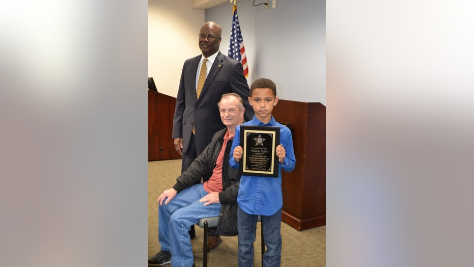 Malachi Coffey (right) stands next to Allen Clemmons (center) and Sumter County Sheriff Anthony Dennis (left). The sheriff's office presented Malachi with a plaque for his heroic deed.