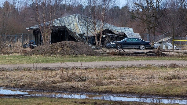 A car sits parked outside the charred remains of a boarding kennel in Fruitport Township, Mich., on Friday, March 30, 2018. Authorities say over two dozen dogs are believed to have died in the early morning fire in western Michigan.  (Cory Morse /The Grand Rapids Press via AP)
