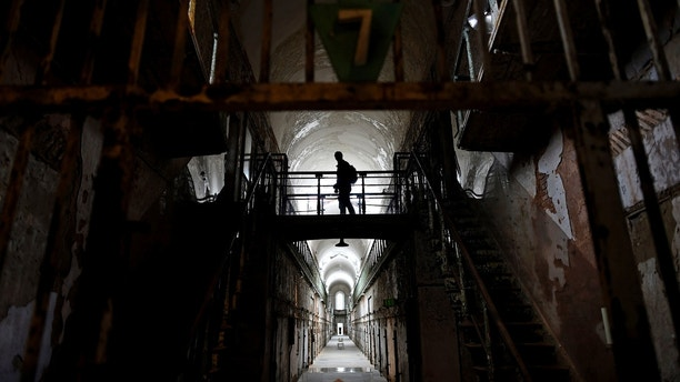 """A visitor wanders through block 7 of Eastern State Penitentiary in Philadelphia, Pennsylvania April 30, 2014. Opened in 1829, with the original corrective system of """"confinement in solitude with labor,"""" the penitentiary housed about 75,000 inmates in its 142 years of operation. At Eastern State reunions, former inmates, staff and guard gather to share memories and trade stories and get a chance to describe their experiences in question-and-answer sessions with the public. Picture taken April 30, 2014.  REUTERS/Mark Makela   (UNITED STATES - Tags: CRIME LAW ANNIVERSARY SOCIETY) - TM4EA4U1LT101"""