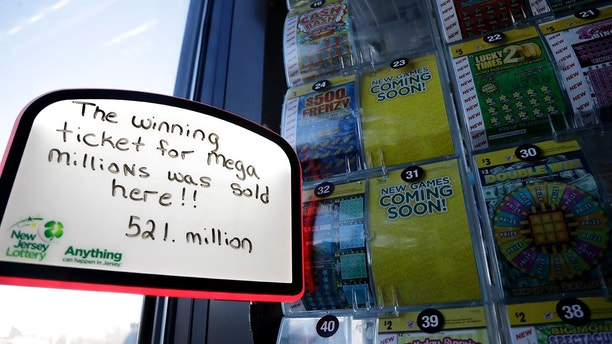 A sign is displayed near scratch-off tickets inside a Lukoil service station where the winning ticket for the Mega Millions lottery drawing was sold, Saturday, March 31, 2018, in Riverdale, N.J. (AP Photo/Julio Cortez)
