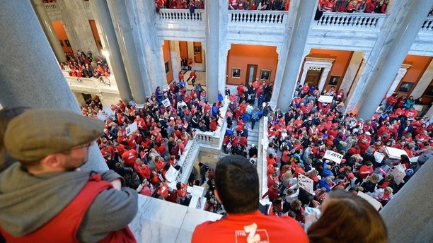 Thousands of teachers from across Kentucky fill the state Capitol to rally for increased funding and to protest last minute changes to their state funded pension system, Monday, April 2, 2018, in Frankfort, Ky. Thousands filled the state Capitol in Kentucky on Monday to protest teacher pension changes, and schools were closed statewide in Oklahoma as thousands more educators rallied for increased education funding. (AP Photo/Timothy D. Easley)