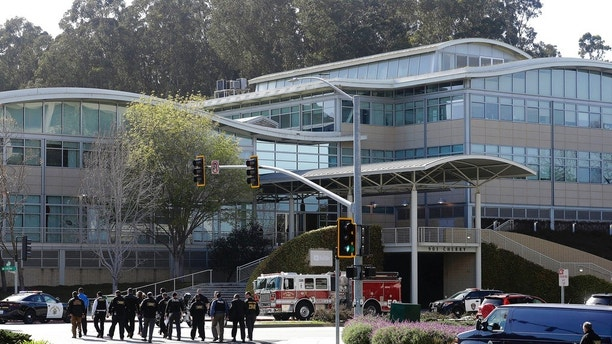 Law enforcement officials walk toward YouTube offices in San Bruno, Calif., Tuesday, April 3, 2018. A woman opened fire Tuesday at YouTube headquarters, wounding some people before fatally shooting herself as terrified employees huddled inside, police and witnesses said. (AP Photo/Jeff Chiu)