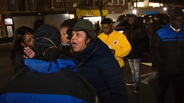 Sandy Michelin, an aunt of Kimani Gray, who was fatally shot by police in 2013, shouts at officers after police shot and killed a man in the Crown Heights neighborhood of Brooklyn, Wednesday, April 4, 2018, in New York, while responding to reports of a man threatening people with a gun. (AP Photo/Kevin Hagen)