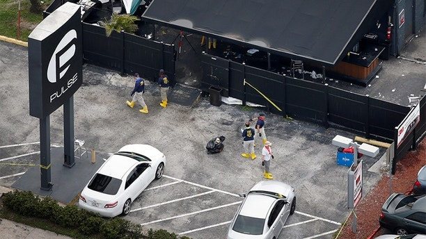 Federal Bureau of Investigation (FBI) officials collect evidence from the parking lot of the Pulse gay night club, the site of a mass shooting days earlier, in Orlando, Florida, U.S., June 15, 2016.  REUTERS/Adrees Latif - S1AETKCSIXAA
