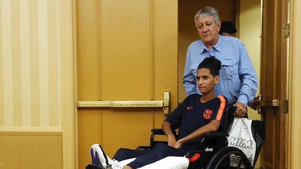 Anthony Borges is pushed by his grandfather Alfredo Borges at the start of a news conference in Plantation, Fla., Friday, April 6, 2018. An attorney for Anthony Borges read a statement from him criticizing Broward Sheriff Scott Israel and School Superintendent Robert Runcie, for the deaths and injuries during the Feb. 14 massacre at Marjory Stoneman Douglas High School in Parkland, Fla. Borges sustained five bullet wounds after he used his body to block a classroom door during the shooting. (AP Photo/Marta Lavandier)
