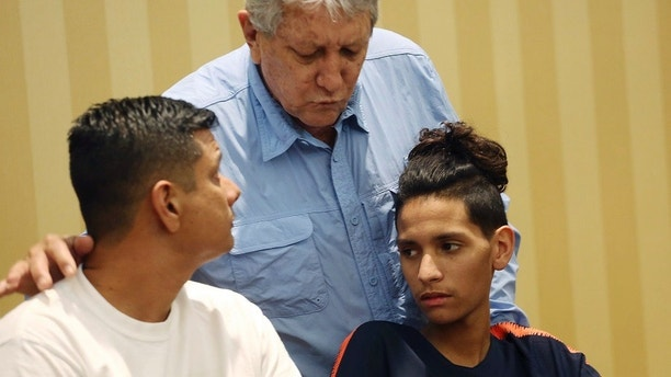 Anthony Borges, right, and his father, Roger, left, listen to his grandfather Alfredo during a news conference in Plantation, Fla., Friday, April 6, 2018. An attorney for Anthony Borges read a statement from him criticizing Broward County Sheriff Scott Israel and School Superintendent Robert Runcie for the deaths and injuries sustained during the Feb. 14 massacre at Marjory Stoneman Douglas High School in Parkland, Fla. Anthony Borges sustained five bullet wounds after he used his body to block a classroom door during the shooting. (AP Photo/Marta Lavandier)