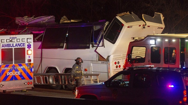 Police and firefighters respond to the scene of a charter bus accident on the eastbound Southern State Parkway in Lakeview, N.Y., Sunday, April 8, 2018. A charter bus carrying teenagers has struck a bridge overpass on Long island, mangling the entire length of the top of the bus. (Howard Schnapp/Newsday via AP)