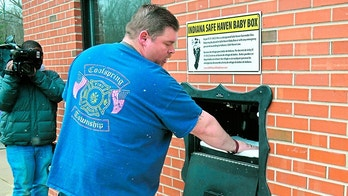 In this Monday, April 9, 2018, photo, Lt. Chuck Kohler, with the Coolspring Township Volunteer Fire Department, shows how a mother can relinquish her newborn, anonymously and without fear of prosecution, using the Safe Haven Baby Box, in Michigan City, Ind. A baby was left inside the box Sunday, and Kohler said he arrived at the station less than a minute after the opening of the box triggered an automatic alarm at the unmanned station. On Nov. 7, another baby girl was safely rescued after being left in the box. (Jon Gard/The News Dispatch via AP)