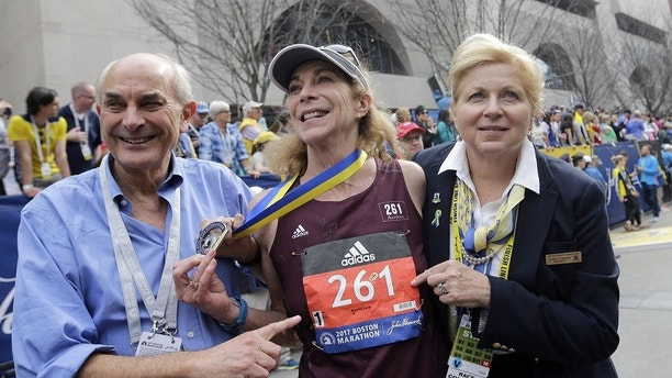 Kathrine Switzer, center, the first official woman entrant in the Boston Marathon 50 years ago, wears the same bib number after finishing the marathon on Monday, April 17, 2017, in Boston. With Switzer are her husband Roger Robinson, left, and Joann Flaminio, right, of the Boston Athletic Association. (AP Photo/Elise Amendola) ORG XMIT: BX150