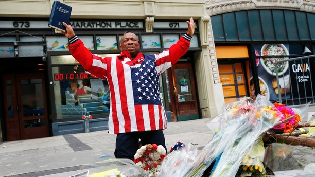 Cristopher Nzenwa, of Boston, prays at the site of the first explosion during the 2013 Boston Marathon, Sunday, April 15, 2018, in Boston. (AP Photo/Michael Dwyer)