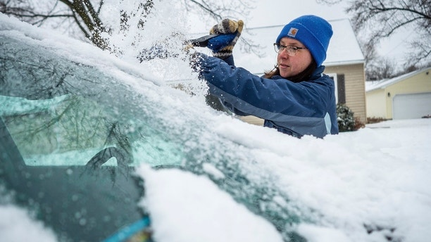 Colleen Streefland brushes snow and ice of her vehicle during a storm Saturday, April 14, 2018, in Rochester, Minn. A storm system stretching from the Gulf Coast to the Great Lakes buffeted the central U.S. with heavy winds, rain, hail and snow, (Joe Ahlquist /The Rochester Post-Bulletin via AP)