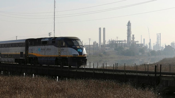 An Amtrak passenger train rolls past the Tesoro refinery in Martinez, California, February 2, 2015. A labor strike that some fear could impact gasoline production at several of the largest U.S. oil refineries and chemical plants stretched into a second day on Monday, as union workers sought a new national contract. One of the affected plants, Tesoro Corp's 166,000-barrel-per-day Martinez, California, refinery, was being fully shut down, since part of it was already in the midst of planned maintenance work. REUTERS/Robert Galbraith  (UNITED STATES - Tags: BUSINESS EMPLOYMENT CIVIL UNREST) - GM1EB230EA601