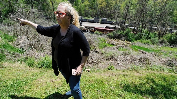 """In this April 12, 2018 photo, Mayor Heather Hall discusses the nearby train that was loaded with tons of sewage sludge that is stinking up her community of Parrish, Ala. More than two months after the so-called """"Poop Train"""" rolled in from New York City, Hall says her small town smells like rotting corpses. Some say the trainloads of New Yorkers' excrement is turning Alabama into a dumping ground for other states' waste. (AP Photo/Jay Reeves)"""