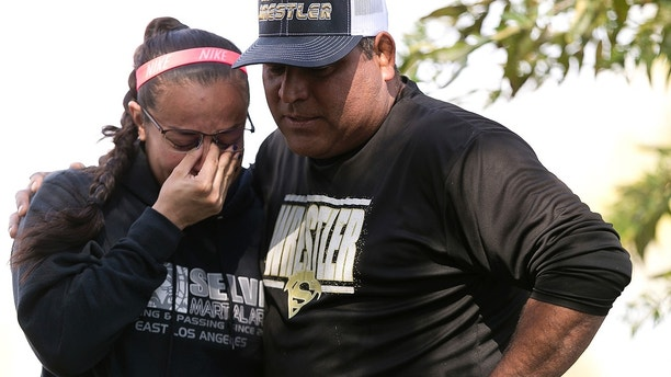 Wrestling coach Ray Castellanos, right, and assistant coach, Monique Cabrera, left, stand at the site where South El Monte High School student, Jeremy Sanchez, a 17-year-old was fatally stabbed by a teenage friend, in South El Monte, Calif., Thursday, April 19, 2018. Los Angeles County sheriff's investigators say a 16-year-old was arrested on suspicion of murder. (AP Photo/Damian Dovarganes)
