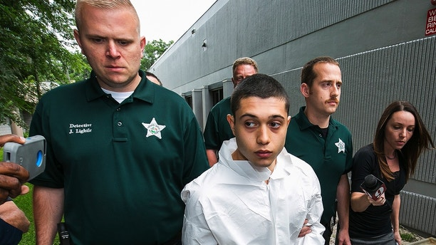 Marion County Sheriff's Detectives John Lightle, left, and Dan Pinder, right, escort a handcuffed and shackled Sky Bouche, 19, center, to a waiting patrol car, Friday, April 20, 2018, in Ocala, Fla. Bouche is the suspect in a shooting that occurred at Forest High School Friday morning. (Doug Engle/Ocala Star-Banner via AP)