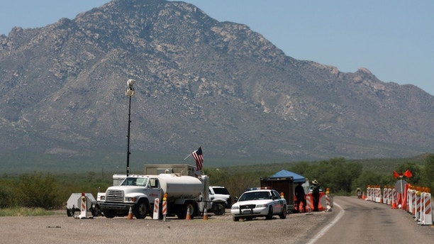 U.S. Border Patrol Agents stand at a checkpoint along a road in Pima County, Arizona August 17, 2009. Picture taken August 17, 2009. REUTERS/Joshua Lott (UNITED STATES CRIME LAW SOCIETY POLITICS EMPLOYMENT BUSINESS) - GM1E58J04BT01