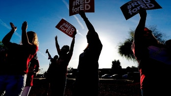File - In this April 11, 2018 file photo, teachers at Humphrey Elementary school participate in a state-wide walk-in prior to classes in Chandler, Ariz. Tens of thousands of Arizona teachers are poised to walk off the job this week to demand more funding for public education, an unprecedented action in a conservative state without many union protections. A chunky-text look at what's happening in the run-up to the first-ever statewide strike. (AP Photo/Matt York, File)