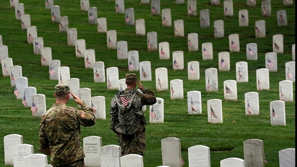"""Soldiers from the 3rd U.S. Infantry Regiment (Old Guard) salute as Taps is heard nearby during """"Flags-in"""", where a flag is placed at each of the 284,000 headstones at Arlington National Cemetery, ahead of Memorial Day, in Arlington, Virginia, U.S., May 25, 2017. REUTERS/Kevin Lamarque - RC1350BC2680"""