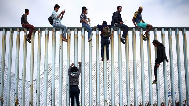 Members of a caravan of migrants from Central America climb up the border fence between Mexico and the U.S., as a part of a demonstration prior to preparations for an asylum request in the U.S., in Tijuana, Mexico April 29, 2018. REUTERS/Edgard Garrido     TPX IMAGES OF THE DAY - RC1D468F1060