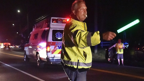 A first responder secures traffic as emergency personnel work the scene of explosion and reported stand-off in North Haven, Conn., Wednesday evening, May 2, 2018. A barn behind a house in Connecticut exploded Wednesday night while police and a SWAT team were negotiating with a man who had taken his wife and family hostage, leaving several officers injured, officials said. (Catherine Avalone/New Haven Register via AP)