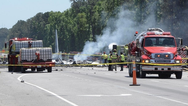 First responders from multiple local and state agencies fight the fires caused by the crash of a C-130 Hercules cargo plane from Puerto Rico Air National Guard Wednesday, May 2, 2018. The plane crashed near the intersection of Ga. 21 and Crossgate Road in Savannah, Ga. (Will Peebles/Savannah Morning News via AP)
