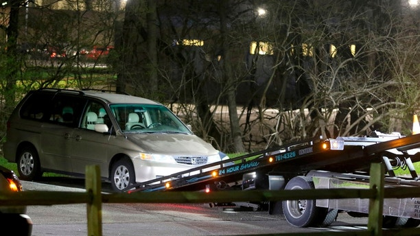 FILE - In this April 10, 2018 photo, a minivan is removed from the parking lot near the Seven Hills School campus in Cincinnati. Cincinnati officials expect to review a plan for improving the city's emergency center while police finish an internal investigation into the death of Kyle Plush who twice called 911 to report he was trapped in a minivan. The city's acting manager says he'll present City Council members Monday, April 30, with planned emergency center changes after the failed response to Plush's calls for help on April 10. (Cara Owsley/The Cincinnati Enquirer via AP, File)