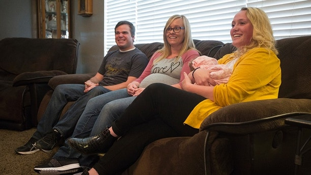 In this Monday, April 30, 2018 photo, from left, Wendell Creager, Laura Creager, Morlie Hayes, 16, and Creager's daughter, Kayla Faith Creager talk at the Hayes' home in Eden, Utah. Hayes unexpectedly delivered her aunt's newborn in the bathroom of her home on Saturday, April 28. (Jacob Wiegand/The Deseret News via AP)