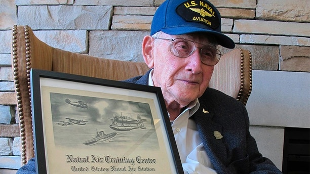 In this Wednesday, April 25, 2018 photo, World War II veteran Bob Barger poses with his Naval flight school certificate in Toledo, Ohio. Barger is set to graduate from the University of Toledo after a review of his transcripts showed he completed enough classes in the late 1940s for a two-year degree. (AP Photo/John Seewer)