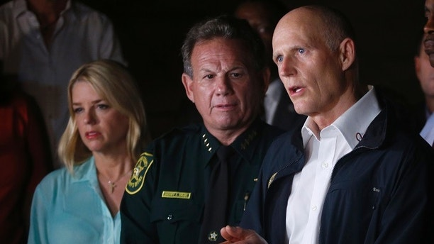 Florida Gov. Rick Scott, foreground, speaks along with Sheriff Scott Israel, center, of Broward County, and Pam Bondi, Florida Attorney General, during a news conference near Marjory Stoneman Douglas High School in Parkland, Fla., where a former student is suspected of killing at least 17 people Wednesday, Feb. 14, 2018. The shooting at a South Florida high school sent students rushing into the streets as SWAT team members swarmed in and locked down the building. Police were warning that the shooter was still at large even as ambulances converged on the scene and emergency workers appeared to be treating those possibly wounded. (AP Photo/Wilfredo Lee)