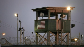 FILE - In this March 29, 2010 photo, reviewed by the U.S. military, a Guantanamo guard keeps watch from a tower overlooking the detention facility at Guantanamo Bay U.S. Naval Base, Cuba. The transfer of prisoners out of Guantanamo Bay has ground to a halt amid a slow Pentagon approval process. That's caused frustration within the administration and raised doubts that President Barack Obama can fulfill his campaign promise to close the U.S. prison Cuba for terrorism suspects. (AP Photo/Brennan Linsley, File)